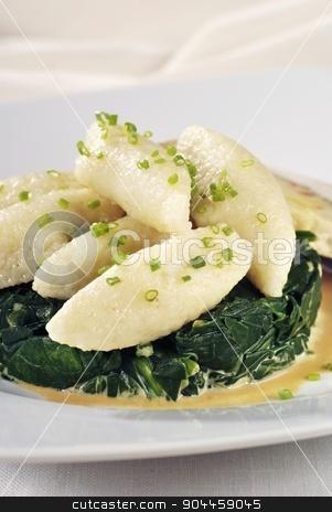 Potato dumplings  stock photo, Potato dumplings on a nest of spinach leaves  by Digifoodstock