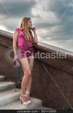 Pretty girl with bouquet over city background stock photo, Young attractive woman in pink with bouquet over city background by Aikon