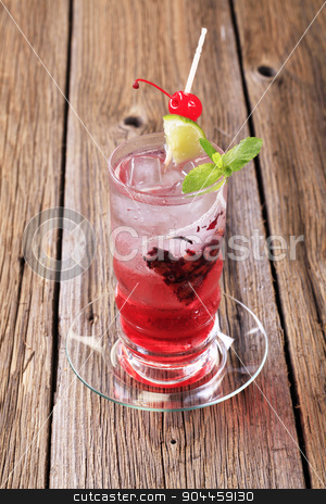 Iced drink stock photo, Glass of iced drink garnished with lime and maraschino cherry by Digifoodstock