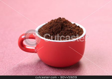 Ground coffee stock photo, Heap of freshly ground coffee in a red cup by Digifoodstock