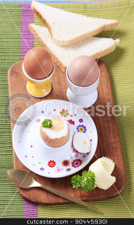 Boiled eggs  stock photo, Three boiled eggs in porcelain eggcups and white bread by Digifoodstock