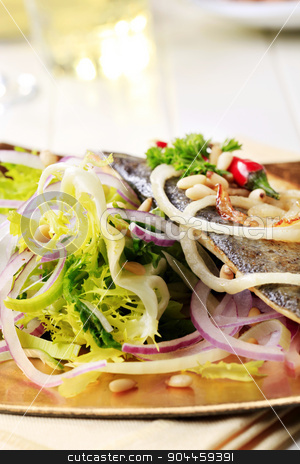 Pan fried trout with green salad stock photo, Pan fried trout fillet garnished with salad greens and onion by Digifoodstock