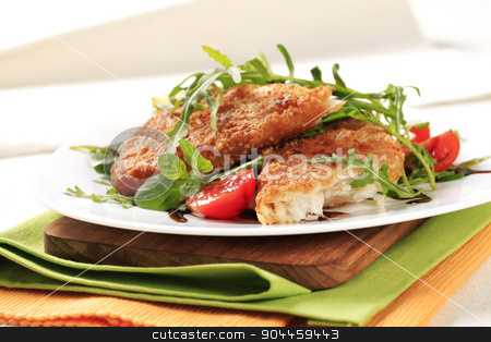 Fried fish and fresh salad stock photo, Fried fish on a bed of fresh salad by Digifoodstock