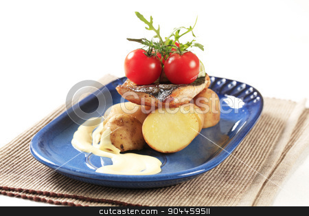 Pan fried fish with new potatoes stock photo, Pan fried fish served with new potatoes by Digifoodstock