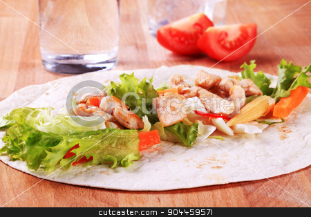 Preparing chicken wrap sandwich stock photo, Grilled chicken strips and fresh vegetables spread on tortilla by Digifoodstock