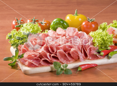 Dry salami stock photo, Slices of dry salami and fresh vegetables  by Digifoodstock