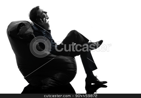 man sitting on the telephone silhouette stock photo, one  man sitting on the telephone in silhouette studio isolated on white background by Ishadow