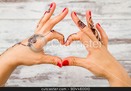 Woman Hand Painted with Floral Figures Using Black Henna  stock photo, Woman hands with nail polish painted with black henna doing heart gesture by OZMedia