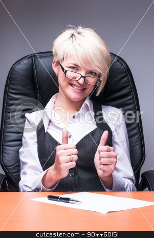 Beautiful smiling business woman shows thumb up stock photo, Attractive blonde smiling business lady shows thumb up by Aikon