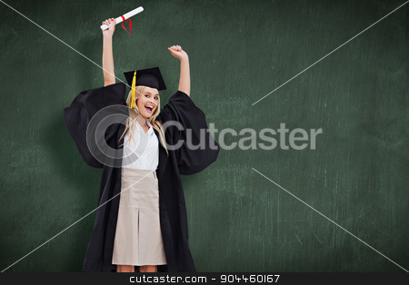 Composite image of blonde student in graduate robe holding up he stock photo, Blonde student in graduate robe holding up her diploma against green chalkboard by Wavebreak Media