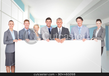 Composite image of smiling business team holding poster stock photo, Smiling business team holding poster against modern blue and white room by Wavebreak Media