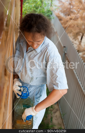 Pretty woman painting her house stock photo, Attractive woman making biochemical impregnation against fire and bugs by Aikon