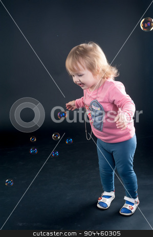 Portrait of adorable young girl stock photo, Little girl catches soap bubbles over black background by Aikon