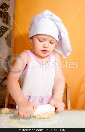 baby girl in cook role stock photo, Cute little cook girl molds cookies from dough by Aikon