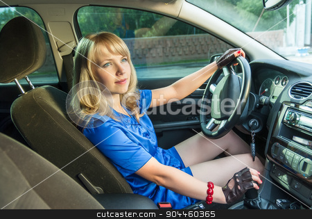 Young attractive woman driving her car stock photo, Pretty blonde girl in blue blouse and shorts driving her car by Aikon