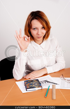 business analyst woman with ok gesture stock photo, caucasian businesswoman sitting at desk in casual clothes. She is analyzing sales statistics and showing ok gesture by Aikon