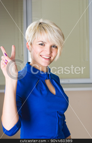 Girl with victory gesture stock photo, Young woman showing victory sign at office background by Aikon