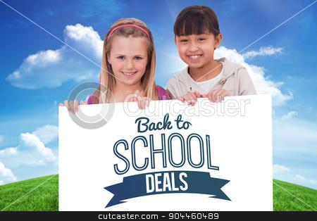Composite image of girls behind a blank panel stock photo, Girls behind a blank panel against green hill under blue sky by Wavebreak Media