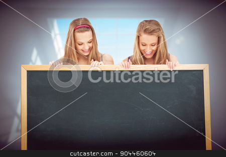 Composite image of close up of two young women holding a blank b stock photo, Close up of two young women holding a blank board against room with large windows by Wavebreak Media