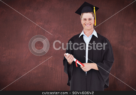 Composite image of a male graduate with his degree in hand stock photo, A male graduate with his degree in hand against desk by Wavebreak Media