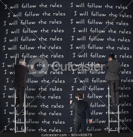 Composite image of business team writing stock photo, Business team writing against blackboard by Wavebreak Media