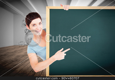 Composite image of beautiful brunette pointing at a blank panel stock photo, Beautiful brunette pointing at a blank panel against doodle office in room by Wavebreak Media