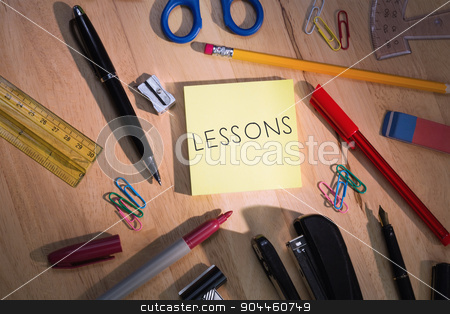 Lessons against students table with school supplies stock photo, The word lessons against students table with school supplies by Wavebreak Media