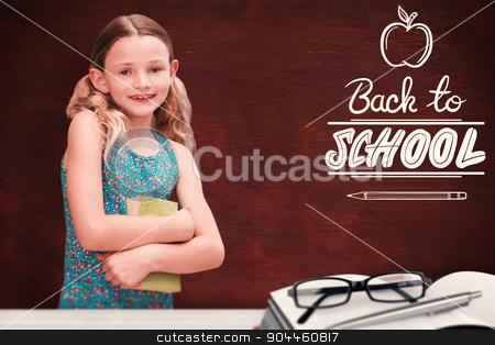Composite image of girl holding book in library stock photo, Girl holding book in library against desk by Wavebreak Media