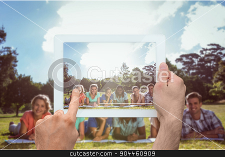 Composite image of hand holding tablet pc stock photo, Hand holding tablet pc against students studying outside on campus by Wavebreak Media