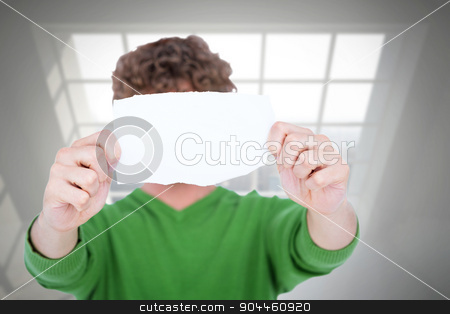 Composite image of man holding blank paper in front on face stock photo, Man holding blank paper in front on face against room overlooking city by Wavebreak Media