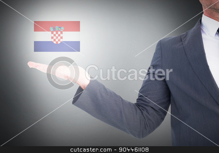 Composite image of businessman with his hand out stock photo, Businessman with his hand out against grey background by Wavebreak Media