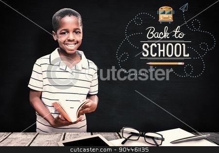 Composite image of happy pupil with book stock photo, happy pupil with book against blackboard by Wavebreak Media
