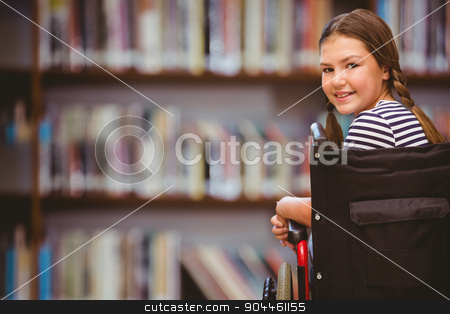Composite image of girl sitting in wheelchair in school stock photo, Girl sitting in wheelchair in school against library shelf by Wavebreak Media