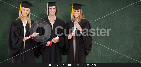 Composite image of three students in graduate robe holding a dip stock photo, Three students in graduate robe holding a diploma against green chalkboard by Wavebreak Media
