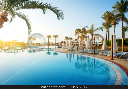 Pool and palms stock photo, Swimming pool and big green palms at sunrise by Givaga