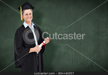Composite image of a smiling man looking at the camera as he gra stock photo, A smiling man looking at the camera as he graduates against green chalkboard by Wavebreak Media