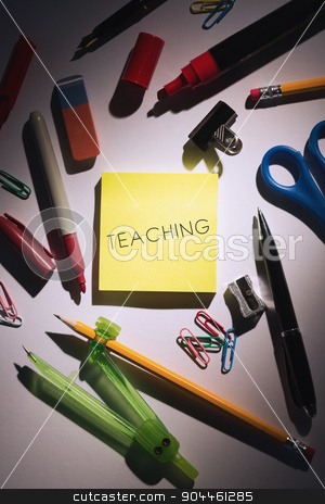 Teaching against students table with school supplies stock photo, The word teaching against students table with school supplies by Wavebreak Media