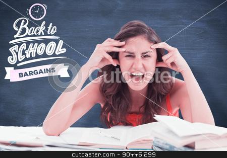 Composite image of student goes crazy doing her homework stock photo, Student goes crazy doing her homework against blue chalkboard by Wavebreak Media