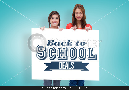Composite image of smiling young women proudly holding a blank p stock photo, Smiling young women proudly holding a blank poster against blue vignette background by Wavebreak Media