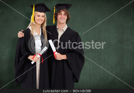 Composite image of two students in graduate robe shoulder to sho stock photo, Two students in graduate robe shoulder to shoulder against green chalkboard by Wavebreak Media