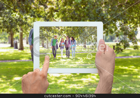 Composite image of hand holding tablet pc stock photo, Hand holding tablet pc against froup of college students walking in the park by Wavebreak Media