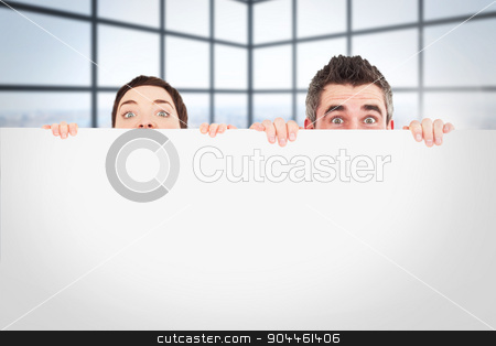 Composite image of man and woman hiding behind a white board wit stock photo, Man and woman hiding behind a white board with room for  copy space against room with large windows showing city by Wavebreak Media