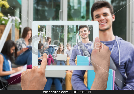 Composite image of hand holding tablet pc stock photo, Hand holding tablet pc against handsome student smiling at camera outside by Wavebreak Media