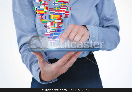 Composite image of businesswoman using her tablet stock photo, Businesswoman using her tablet against international flags by Wavebreak Media