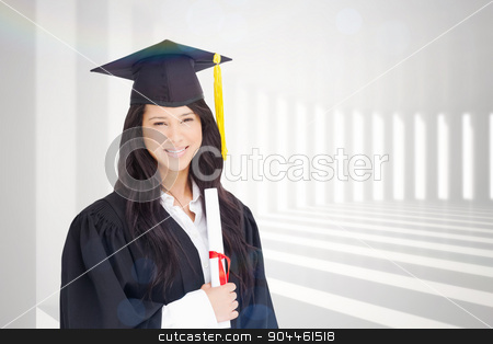 Composite image of a woman standing to the side slightly with he stock photo, A woman standing to the side slightly with her degree and dressed in her graduation robe against curved white room by Wavebreak Media