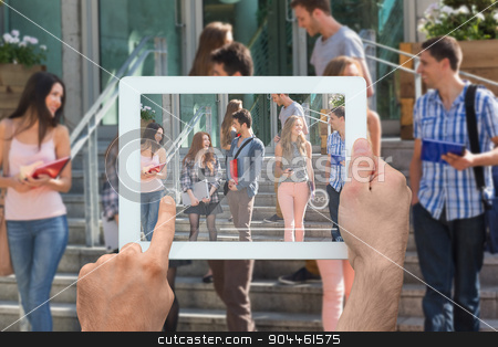 Composite image of hand holding tablet pc stock photo, Hand holding tablet pc against happy students walking and chatting outside by Wavebreak Media