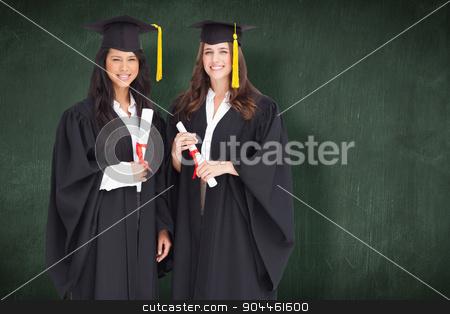 Composite image of full length shot of two women graduating stock photo, Full length shot of two women graduating against green chalkboard by Wavebreak Media