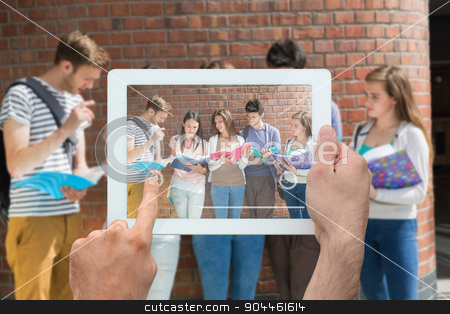 Composite image of hand holding tablet pc stock photo, Hand holding tablet pc against happy students standing and reading by Wavebreak Media