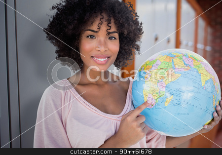Composite image of happy woman pointing to globe stock photo, Happy woman pointing to globe against closed lockers in a row at the college by Wavebreak Media