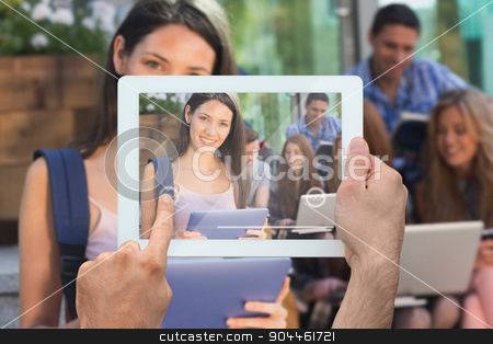 Composite image of hand holding tablet pc stock photo, Hand holding tablet pc against pretty student using her tablet pc on campus by Wavebreak Media